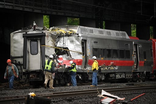 Metro-North employees work at the site of Friday's train derailment in Bridgeport. Conn. on Sunday, May 19, 2013. (AP Photo/The Connecticut Post,Brian A. Pounds)