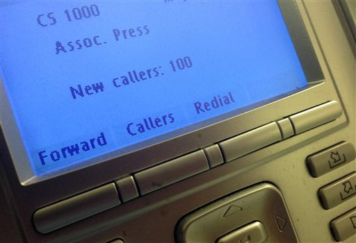 In this May 13, 2013, file photo, the screen on the phone console is seen at the reception desk at The Associated Press Washington bureau.
