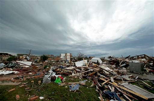 Storm clouds build in the distance beyond tornado-ravaged homes Tuesday, May 21, 2013, in Moore, Okla. (AP Photo/Charlie Riedel)