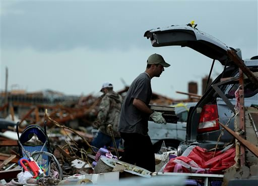 Justin Stehan salvages photographs from his tornado-ravaged home Tuesday, May 21, 2013, in Moore, Okla. (AP Photo/Charlie Riedel)