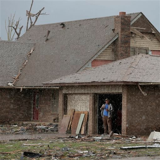 An unidentified man watches a rain storm from inside the garage of his tornado-damaged home Tuesday, May 21, 2013, in Moore, Okla. (AP Photo/Charlie Riedel)