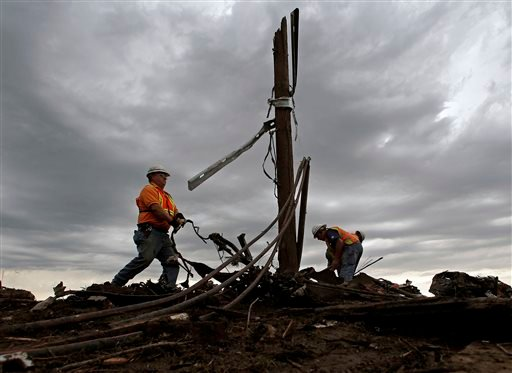 AT&T employees sort through tangled phone lines as they clean up in a tornado-ravaged neighborhood Tuesday, May 21, 2013, in Moore, Okla. (AP Photo/Charlie Riedel)