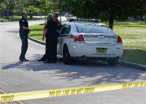 Police officers block the entrance to an apartment complex where man was fatally shot, Wednesday, May 22, 2013, in Orlando, Fla. (AP Photo/John Raoux)