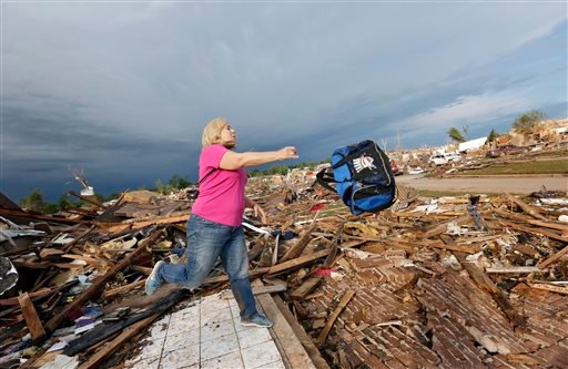 Penny Phillips throws out a bag of salvaged clothing as she goes through the remains of her home on Tuesday, May 21, 2013 in Moore, Okla. that was destroyed by Monday's tornado in the area near 4th and Bryant. (AP Photo/The Oklahoman, Chris Landsberger)