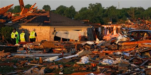 At sunrise, police patrol a partially-destroyed row of houses adjacent to a group of homes completely leveled on Monday when a tornado moved through Moore, Okla., Wednesday, May 22, 2013. (AP Photo/Brennan Linsley)