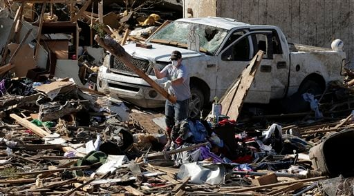 An unidentified man tosses a board as residents sort through their tornado-ravaged homes Wednesday, May 22, 2013, in Moore, Okla. (AP Photo/Charlie Riedel)