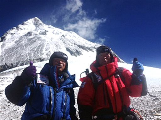 In this May 22, 2013 photo distributed by Miura Dolphins Co. Ltd., 80-year-old Japanese extreme skier Yuichiro Miura, right, and his son, Gota pose at their South Col camp. (AP Photo/Miura Dolphins Co. Ltd.)