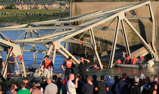 In this photo provided by Francisco Rodriguez, rescue workers surround the scene where a pickup truck and a car fell into the Skagit River after the collapse of the Interstate 5 bridge May 23, 2013, in Mount Vernon, Wash. (AP Photo/Francisco Rodriguez)