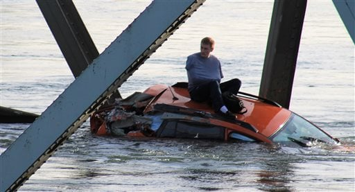 Photo provided by Francisco Rodriguez, a man is seen sitting atop a car that fell into the Skagit River after the collapse of the Interstate 5 bridge there minutes earlier Thursday, May 23, 2013, in Mount Vernon, Wash. (AP Photo/Francisco Rodriguez)
