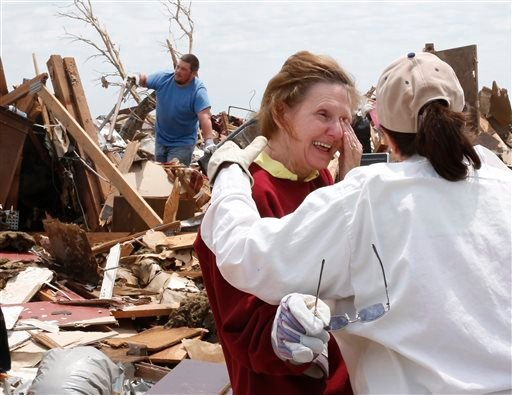 Christine Jones, center, is comforted by her cousin, Ann Worden, right, as she both smiles and wipes away the tears as she talks about looking for lost wedding rings at her tornado demolished home in Moore May 23, 2013.(AP Photo/Sue Ogrocki)