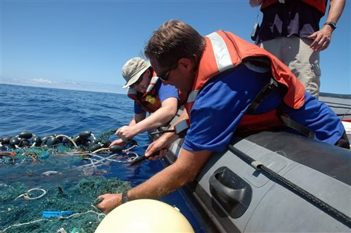 In this Aug. 11, 2009 file photo provided by the Scripps Institution of Oceanography shows Matt Durham, center, pulling in a large patch of sea garbage with the help of Miriam Goldstein, right, in the Pacific Ocean.