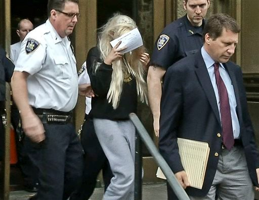 In an image made from video, actress Amanda Bynes, center, wearing sweats and a blonde wig, shields her face as she is escorted after a Manhattan criminal court appearance on Friday May 24, 2013 in New York.