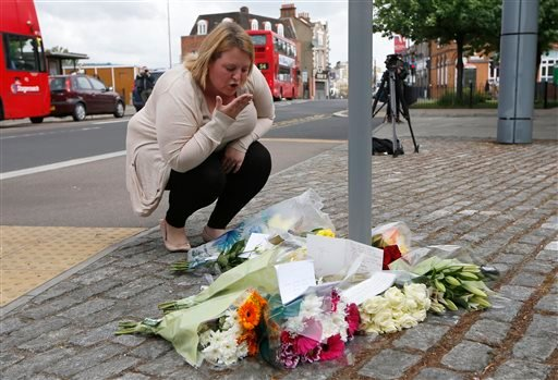 A woman blows a kiss as she lays a floral tribute in memory of the victim outside the Royal Artillery Barracks near the scene of a terror attack in Woolwich, southeast London, Thursday, May 23, 2013.