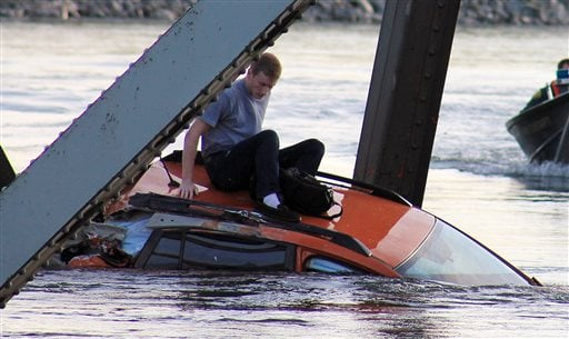 In this photo provided by Francisco Rodriguez, Bryce Kenning sits atop his car that fell into the Skagit River after the collapse of the Interstate 5 bridge there minutes earlier Thursday, May 23, 2013, in Mount Vernon, Wash.