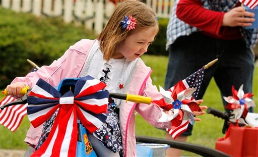 Relariel Webster, 6, of Hartford adjusts her pinwheels before the Memorial Day parade in West Bend on Monday, May 27, 2013. (AP Photo/The Daily News, John Ehlke)