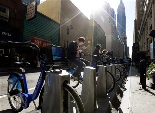 Tourists sit on bikes that are available as part of a bike share program Monday, May 27, 2013, in New York. (AP)