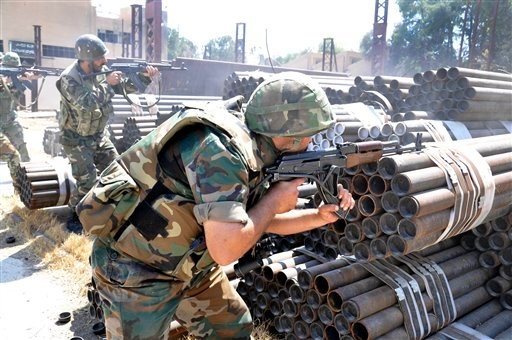 In this photo released on Sunday, May 26, 2013, by the Syrian official news agency SANA, Syrian forces loyal to Syrian President Bashar Assad take their position during a clashes against Syrian rebels, in Aleppo, Syria.