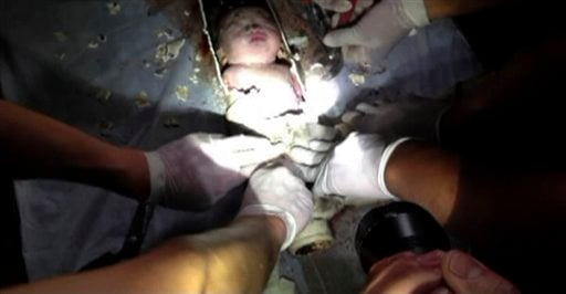 In this still image taken from video from Saturday May 25, 2013, rescue workers cut away the section of a sewage pipe where a newborn baby was trapped in Pujiang in east China's Zhejiang province.
