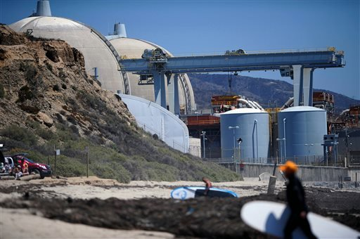 In this July 19, 2012 file photo, surfers walk along a beach nearby the San Onofre Nuclear Power Plant in San Onofre, Calif.