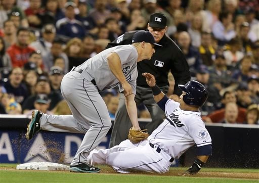 San Diego Padres' Everth Cabrera is out trying to steal third as Seattle Mariners third baseman Kyle Seager applies the tag and umpire Ted Barrettt watches during the fourth inning of a baseball game in San Diego May 29, 2013. (AP Photo/Lenny Ignelzi)