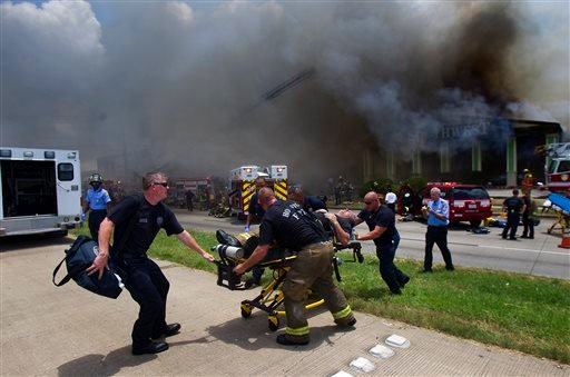 A firefighter is wheeled to an ambulance after fighting a fire at the Southwest Inn, Friday, May 31, 2013, in Houston. (AP)