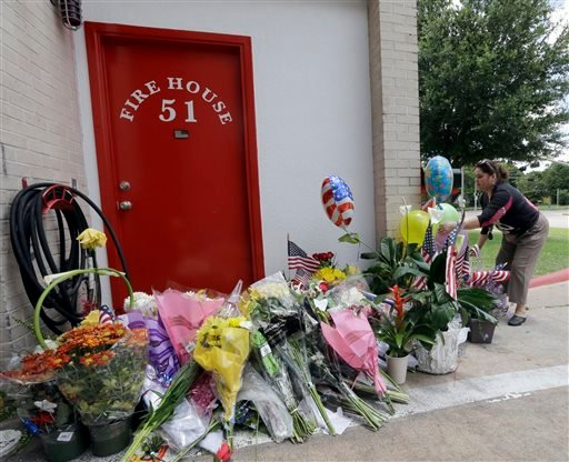 Rafala Santos places flowers at a makeshift memorial at Houston Fire Station 51, Saturday, June 1, 2013, in Houston.