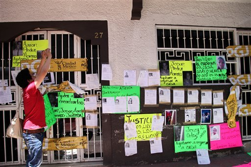 A man takes photos with his mobile phone of the facade of an after hours bar plastered with signs of missing people in Mexico City, Friday May 31, 2013.
