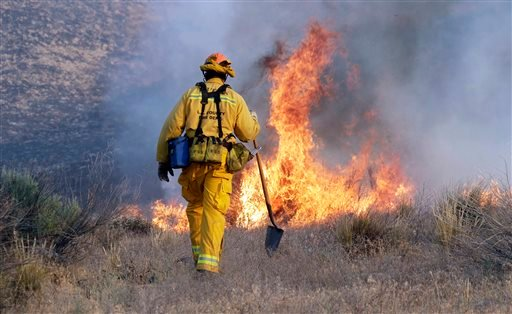 A Los Angeles County firefighter approaches a fire along a road in Lake Hughes, Calif., early Sunday, June 2, 2013.