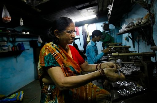 In this Monday, May 20, 2013 photo, Shanti Devi Maurya, who was suffering from cervical cancer, works at her workshop in a slum in Mumbai, India.