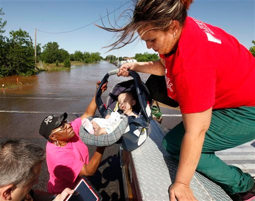 Riley Webb hands her seven month old baby Bryce Webb down to Oklahoma County Commissioner Willa Johnson after being rescued by Midwest City Fire Dept. personnel .