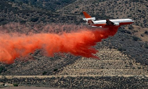 A DC-10 aerial tanker drops a line of fire retardant along the foothills of the Angeles National Forest where it becomes the Antelope Valley in an attempt to stop the Power Station fire if it comes that far, in Lancaster, Calif., Sunday, June 2, 2013.