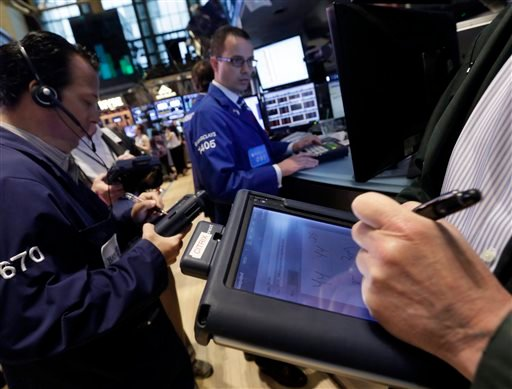 In this Friday, May 31, 2013, photo, traders use their handheld devices as they work on the floor of the New York Stock Exchange. (AP Photo/Richard Drew)