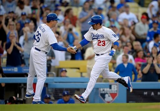 Los Angeles Dodgers' Adrian Gonzalez, right, is congratulated by third base coach Tim Wallach after hitting a solo home run during the first inning of their baseball game against the San Diego Padres, Monday, June 3, 2013, in Los Angeles.