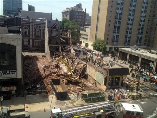 Emergency personnel respond to a building collapse in downtown Philadelphia, where the city fire commissioner says as many as eight to 10 people are believed trapped in the rubble, Wednesday, June 5, 2013. (AP Photo/Dino Hazell)