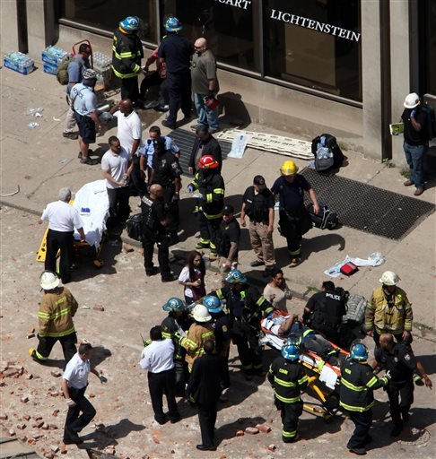 Rescue personnel evacuate an injured person from the scene of a building collapse in downtown Philadelphia, Wednesday, June 5, 2013.