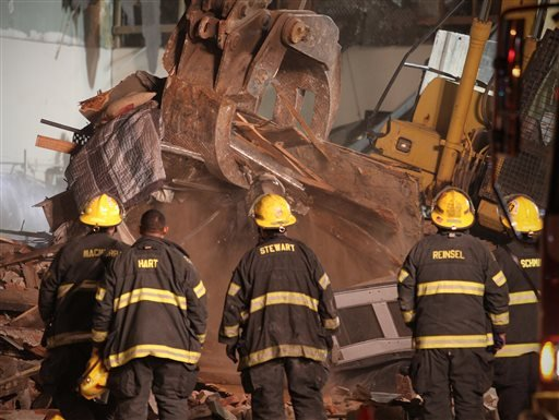 Firefighters watch as the crane pulls debris away from the the site of the collapsed building in Philadelphia, on Wednesday, June 5, 2013.  (AP Photo/Philadelphia Daily News, Stephanie Aaronson)