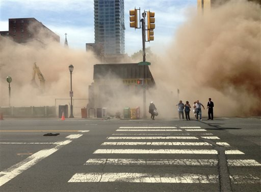 In this photo provided by Jordan McLaughlin, a dust cloud rises as people run from the scene of a building collapse on the edge of downtown Philadelphia on Wednesday, June 5, 2013. (AP Photo/Jordan McLaughlin)