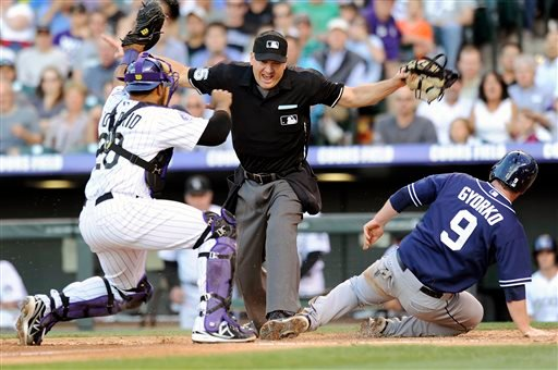 San Diego Padres Jedd Gyorko, right, beats the tag by Colorado Rockies catcher Wilin Rosario, left, and is called safe by the umpire to score in the fourth inning of a baseball game on Thursday, June 6, 2013, in Denver. (AP Photo/Chris Schneider)