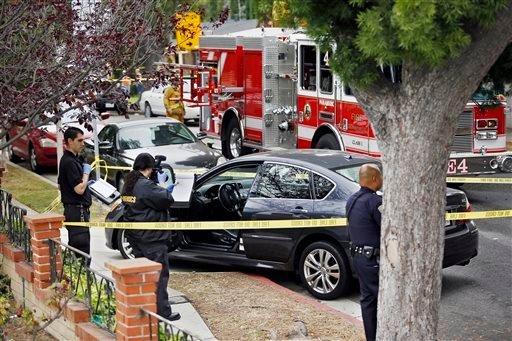 Forensic investigators photograph a car with bullet holes across a home that caught fire in Santa Monica, Calif. Friday, June 7, 2013. (AP)