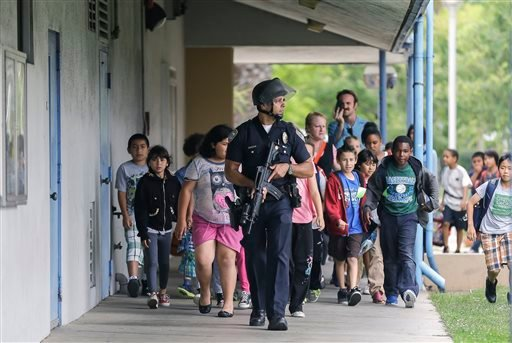 A Santa Monica police officer leads children on a field trip from Citizens of the World Charter School in Los Angeles out of Santa Monica College. (AP Photo/Reed Saxon)