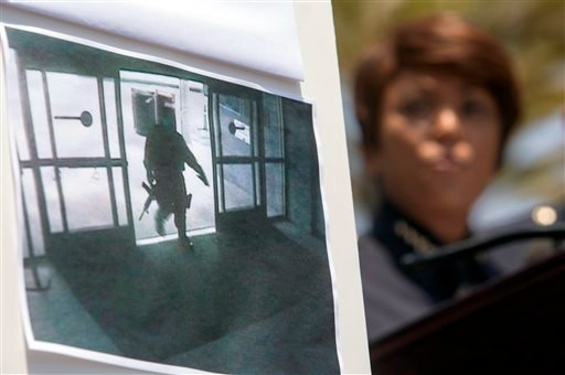 A picture of the suspect entering Santa Monica College Library is seen as Jacqueline Seabrook, Chief of Santa Monica Police department speaks during a news conference Saturday June 8, 2013, in Santa Monica. (AP Photo/Ringo H.W. Chiu)