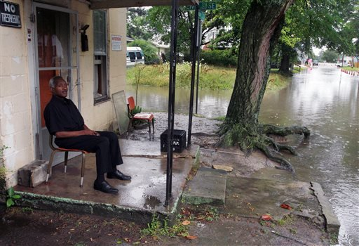 Lee Tillery sits on the porch of his Singletary Street home surrounded by flooded streets in Wilson, N.C.,after heavy rains sweep across the region, Friday, June 7, 2013. (AP Photo/ The Wilson Times, Gray Whitley)