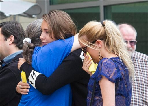 Students and faculty members of Santa Monica College comfort each other at Santa Monica College on Sunday, June 9, 2013 in Santa Monica, Calif. A fatal shooting on Friday left multiple people dead, including the suspected gunman.
