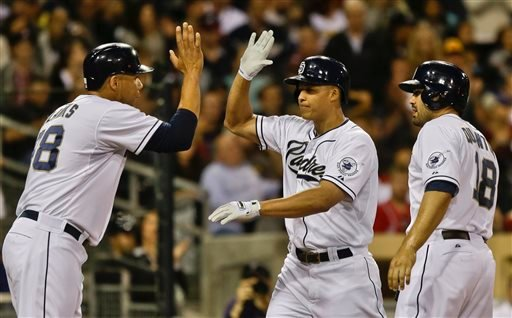 San Diego Padres' Will Venable, center, is congratulated by Kyle Blanks, left, and Carlos Quentin, right, after his three-run home run against the Atlanta Braves in the fourth inning of a baseball game in San Diego, Monday, June 10, 2013.