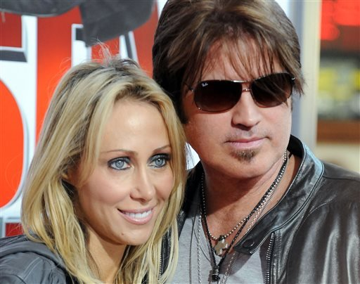 "FILE - In this Jan. 9, 2010 file photo, Billy Ray Cyrus, at right, and his wife Laeticia ""Tish"" Cyrus, arrive to the premiere of ""The Spy Next Door"" in Los Angeles. (AP)"