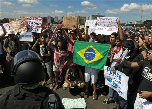"Demonstrators protest in front of the National Stadium, some holding signs that read in Portuguese; ""We don't want stadiums, we want more hospitals,' and ""We don't need stadiums, we need education, health and security."""