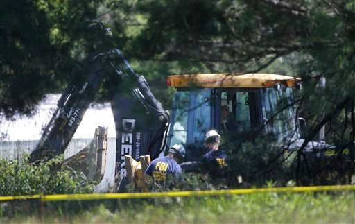 Members of an FBI evidence response team look over an area being cleared in Oakland Township, Mich., Tuesday, June 18, 2013. (AP)
