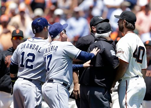 San Francisco Giants starting pitcher Madison Bumgarner, right, is restrained by a pair of umpires after throwing a close pitch to the San Diego Padres' Jesus Guzman during the second inning of their baseball game.