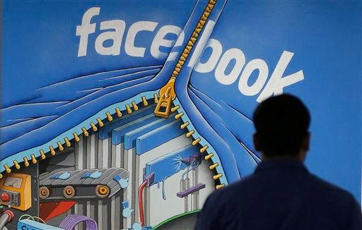 A Facebook employee walks past a sign at Facebook headquarters in Menlo Park, Calif. Facebook on Friday, June 21, 2013 said a bug in its system caused 6 million users' contact information to be inadvertently exposed.