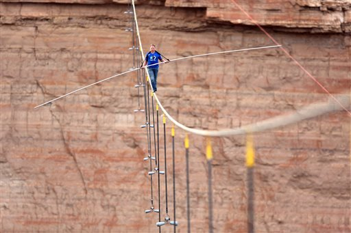 In this photo provided by the Discovery Channel, aerialist Nik Wallenda walks a 2-inch-thick steel cable taking him a quarter mile over the Little Colorado River Gorge, Ariz. on Sunday, June 23, 2013.